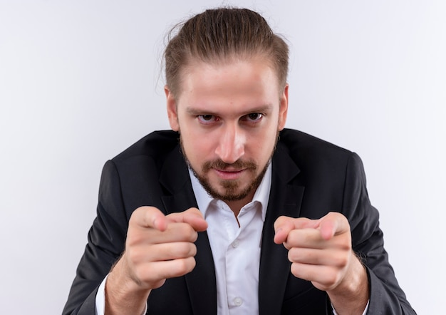 Bel uomo d'affari che indossa tuta che punta con il dito indice alla telecamera con grave in piedi su sfondo bianco