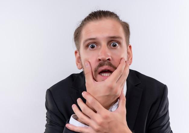 Bel uomo d'affari che indossa tuta scioccato tenendo il viso con la mano in piedi su sfondo bianco