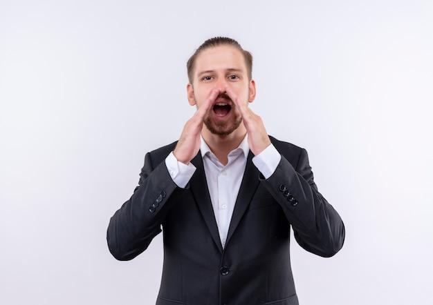 Bel uomo d'affari che indossa tuta gridando o chiamando qualcuno con le mani vicino alla bocca in piedi su sfondo bianco