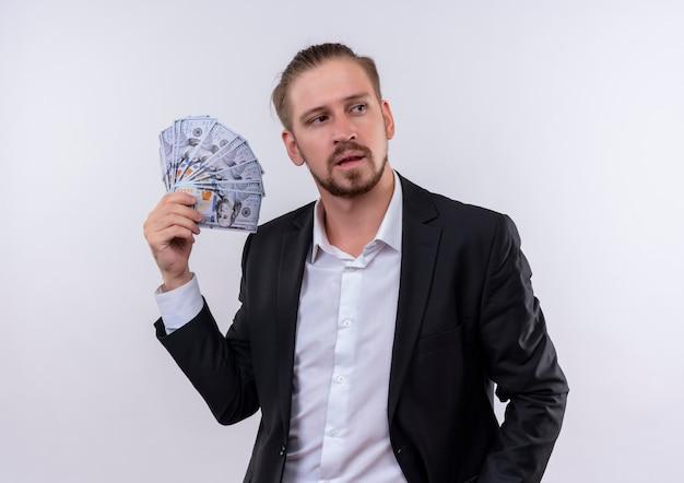 Красивый деловой человек в костюме показывает наличные деньги, глядя в сторону с уверенным выражением лица, стоя на белом фоне