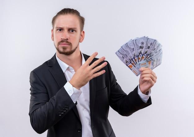흰색 배경 위에 4 번 서를 보여주는 심각한 얼굴로 카메라를보고 현금을 보여주는 양복을 입고 잘 생긴 비즈니스 남자