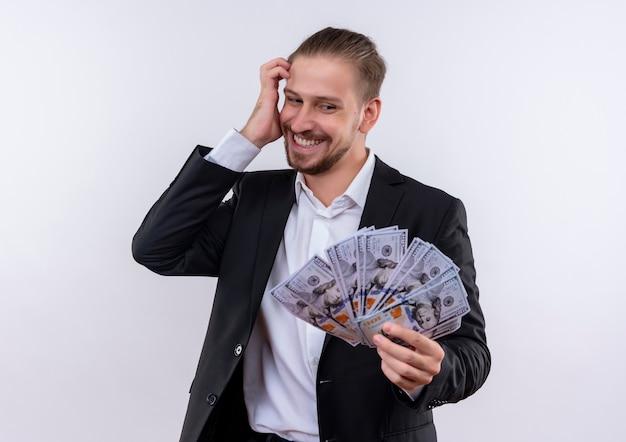 白い背景の上に立って幸せで興奮してお金を見て現金を示すスーツを着てハンサムなビジネス男