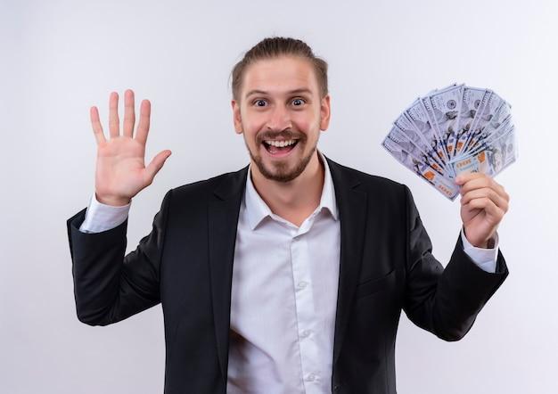 Bel uomo d'affari che indossa tuta che mostra contanti guardando la fotocamera felice ed eccitatowaving con la mano in piedi su sfondo bianco