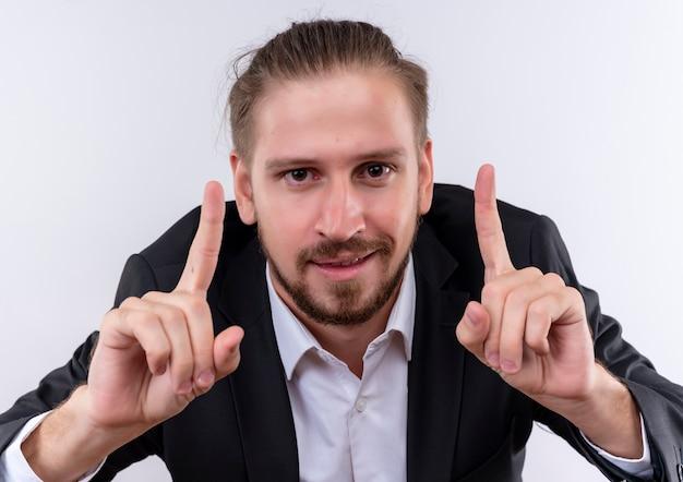 白い背景の上に立って自信を持って見える人差し指の警告を示すスーツを着ているハンサムなビジネスマン