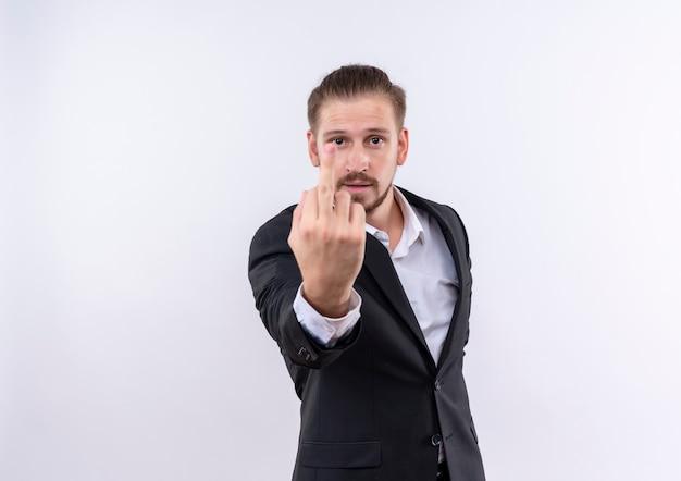 Bel uomo d'affari che indossa tuta che mostra il dito medio in piedi su sfondo bianco