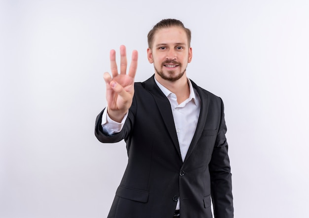 Handsome business man wearing suit showing and pointing up with fingers number three standing over white background