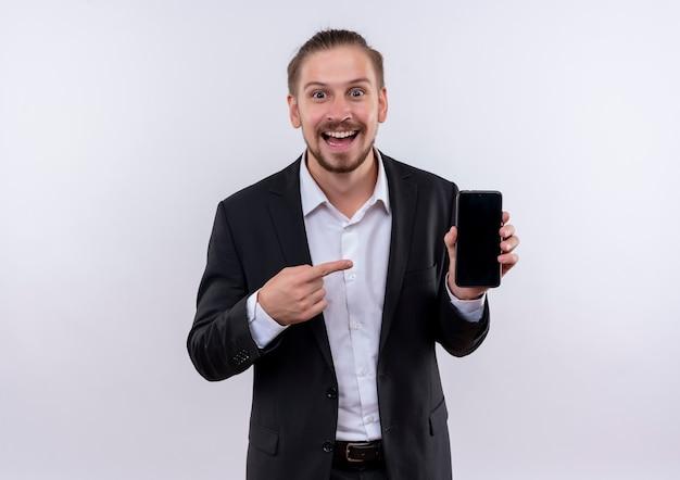 白い背景の上に元気に立って笑ってそれに指で指しているスマートフォンを示すスーツを着ているハンサムなビジネスマン