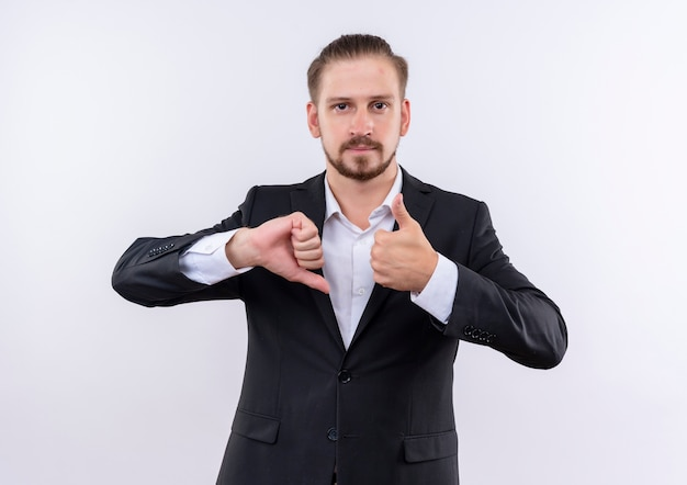 Bel uomo d'affari che indossa tuta che mostra i pollici in su e in giù in piedi su sfondo bianco