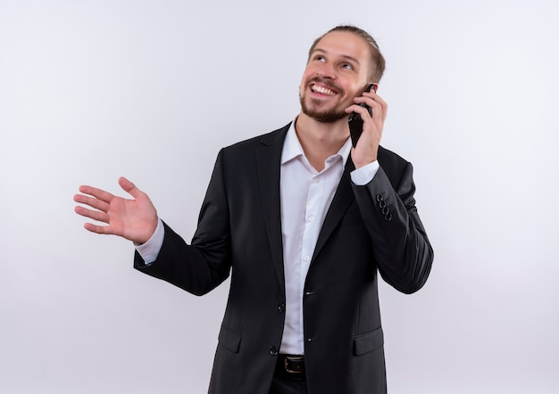Bel uomo d'affari che indossa tuta parlando al telefono cellulare sorridente in piedi su sfondo bianco