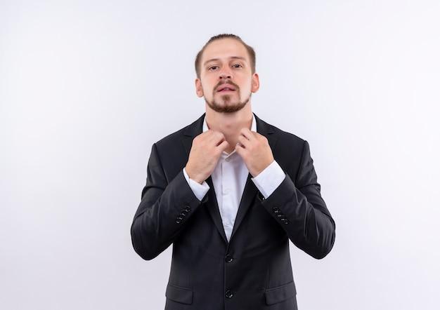 흰색 배경 위에 자신감 서 찾고 그의 칼라를 만지고 양복을 입고 잘 생긴 비즈니스 남자