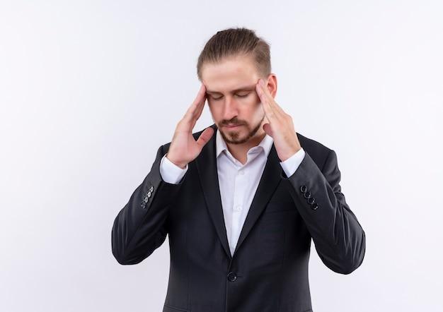 白い背景の上に立っている頭痛を持って疲れて過労に見える彼のこめかみに触れるスーツを着ているハンサムなビジネスマン