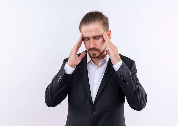 Handsome business man wearing suit touching his temples looking tired and overworked having headache standing over white background