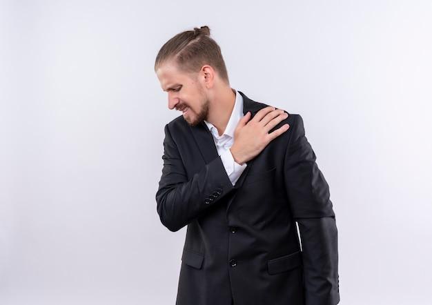 白い背景の上に立っている痛みを感じて肩に触れるスーツを着ているハンサムなビジネスマン