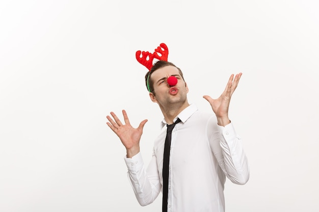 Handsome business man wearinging reindeer hairband making funny facial expression isolated on white.