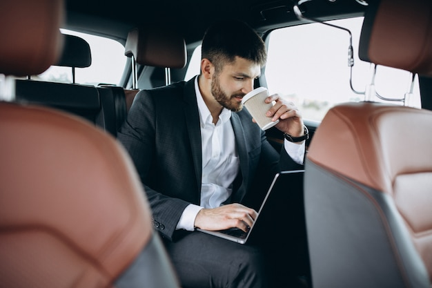 Handsome business man working on a computer in car