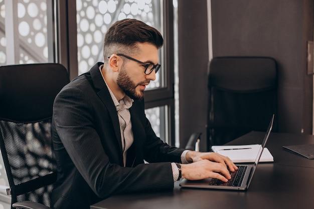 コンピューターに取り組んでいるハンサムなビジネスマン