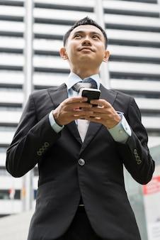 電話でメールやメッセージを書くハンサムなビジネスマン、モデルはアジア人男性です