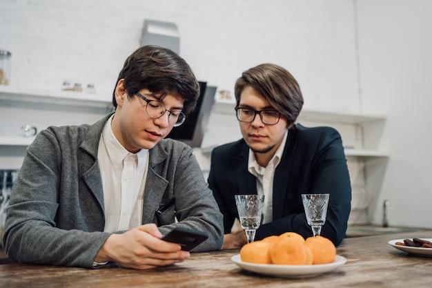 オフィスのキッチンで話しているハンサムなビジネス人々