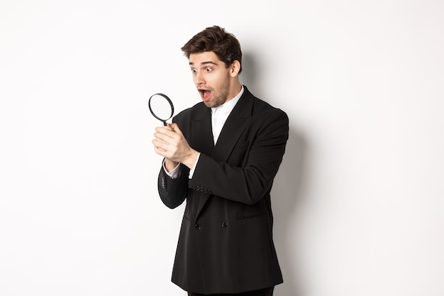 Handsome businessman in black suit, holding magnifying glass and smiling, found something, standing against white background.