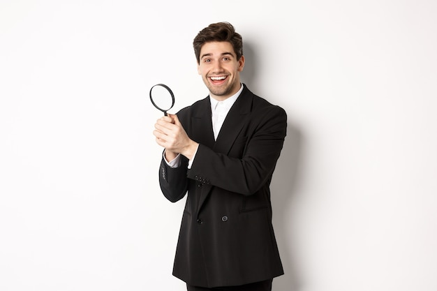 Handsome businessman in black suit, holding magnifying glass and smiling, looking for you, standing against white background.