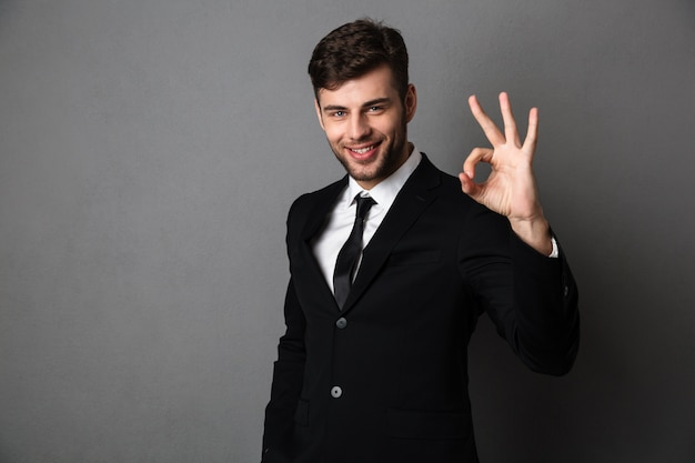 Handsome businessman in black suit showing ok gesture,