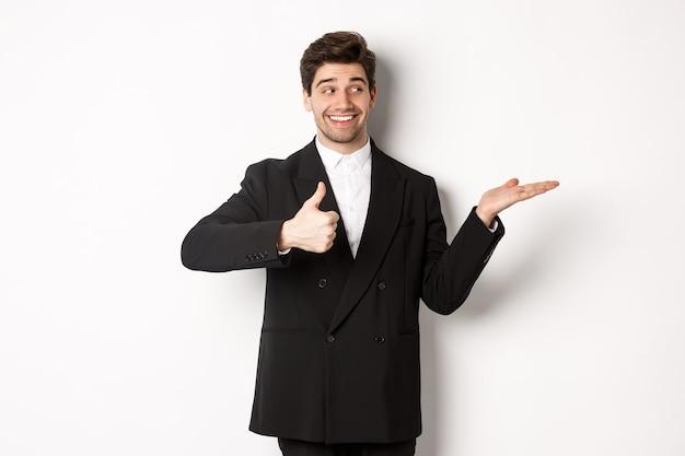 Bello uomo d'affari in abito nero, che mostra il pollice in su e tiene in mano il prodotto sullo spazio bianco della copia, in piedi su sfondo bianco.