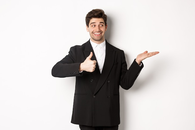 Handsome businessman in black suit, showing thumb-up and holding your product in hand over white copy space, standing against white background