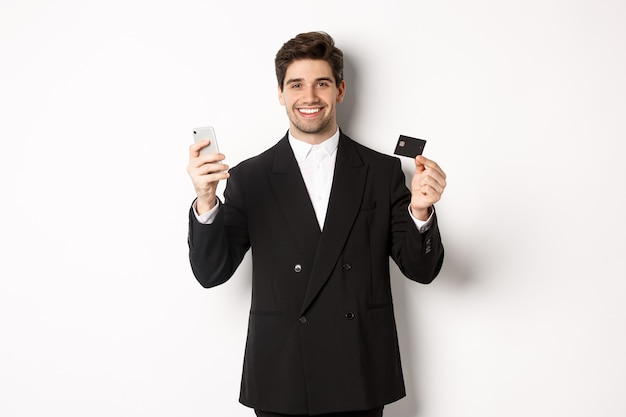 Bello uomo d'affari in abito nero sorridente, mostrando carta di credito e denaro, in piedi su sfondo bianco.