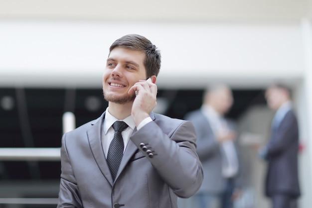 Handsome businessman on blurred office background.
