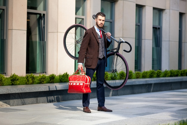 Handsome businessman carrying his bicycle in office