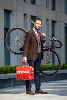 彼の自転車を運ぶハンサムなビジネスマン
