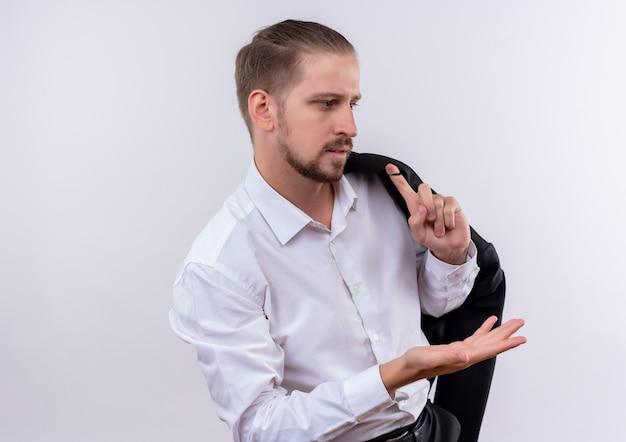 白い背景の上に立って混乱して腕を脇に見て肩に彼のジャケットを運ぶハンサムなビジネスマン