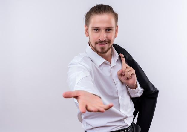 白い背景の上に立っている手を提供するフレンドリーな笑顔のカメラを見て肩に彼のジャケットを運ぶハンサムなビジネスマン