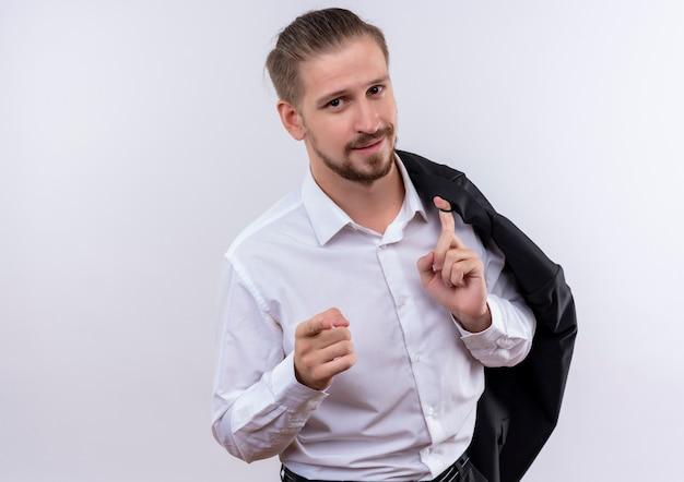 白い背景の上に立っているカメラにfigerを指して自信を持って笑顔でカメラを見て肩に彼のジャケットを運ぶハンサムなビジネスマン