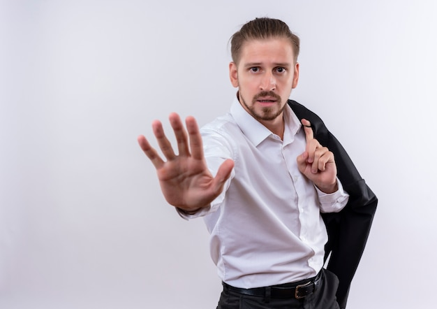 Красивый бизнесмен, несущий куртку на плече, делая знак остановки рукой, смотрящей с серьезным лицом, стоящим на белом фоне