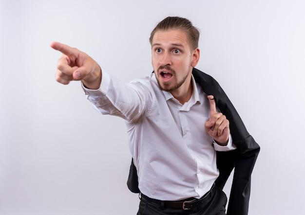 白い背景の上に立って驚いた側に指で指している肩に彼のジャケットを運ぶハンサムなビジネスマン