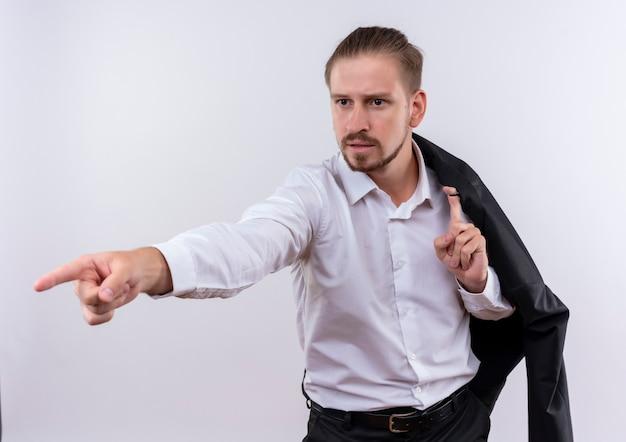 白い背景の上に立っている深刻な顔で横に指で指している肩に彼のジャケットを運ぶハンサムなビジネスマン