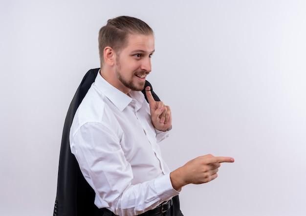 白い背景の上に立っている側に指を指して脇を見て笑って肩に彼のジャケットを運ぶハンサムなビジネスマン