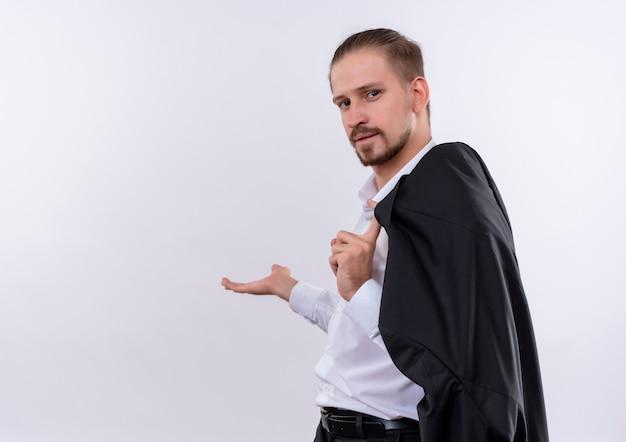 白い背景の上に立っている彼の手の腕で何かを提示笑顔で彼のジャケットを肩に運ぶハンサムなビジネスマン