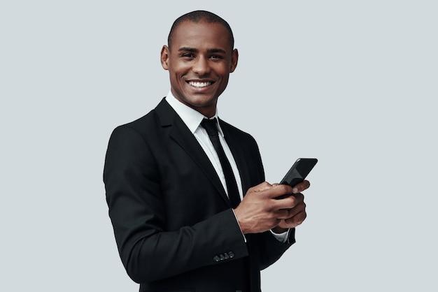 잘생긴 사업가입니다. 스마트 폰을 사용하고 회색 배경에 서서 웃고 있는 정장 차림의 매력적인 젊은 아프리카 남자