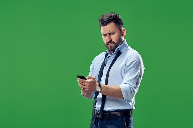 Handsome businessman checking emails on phone. serious business man standing isolated on green. beautiful male half-length portrait