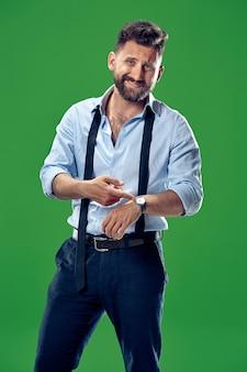 緑に分離された彼の腕時計をチェックするハンサムなビジネスマン