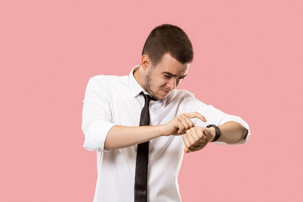 Handsome businessman checking his wrist-watch isolated on pink.