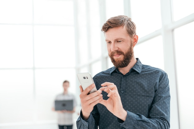 Handsome businessman choosing a contact number in his smartphone