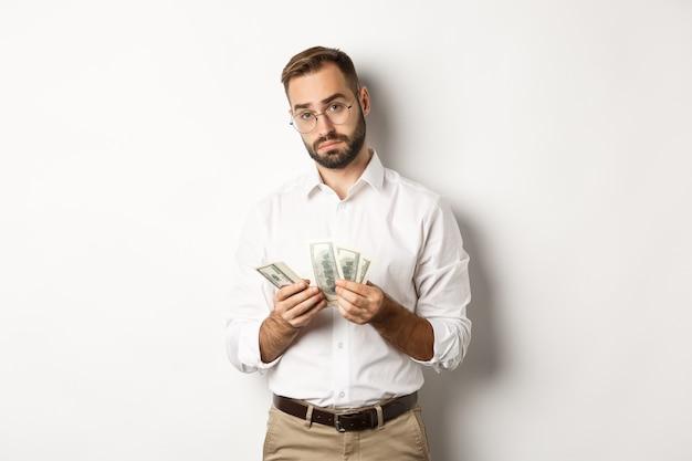 お金を数え、カメラを見て、白い背景に真剣に立っているハンサムなビジネスマン。