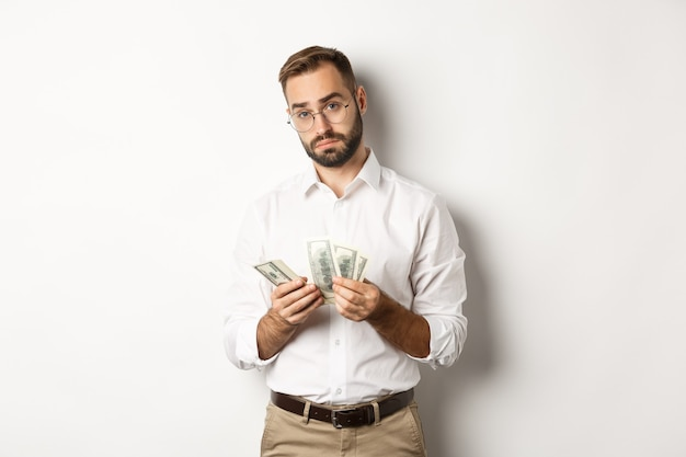 Handsome businessman counting money and looking at camera, standing serious against white background.