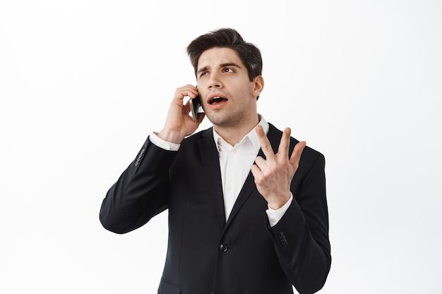 전화 통화 중 손가락을 세고 있는 잘생긴 사업가, 스마트폰에서 주문 번호, 흰 벽 위에 서 있는