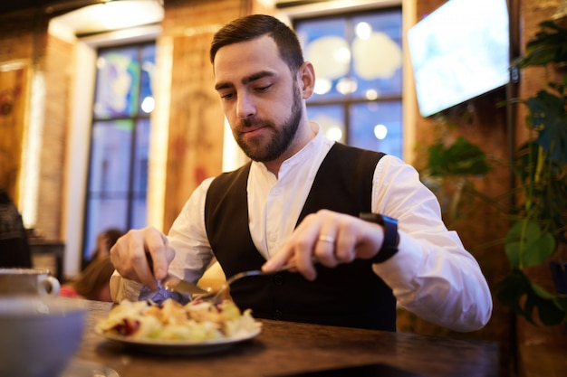 Handsome businessman eating in restaurant