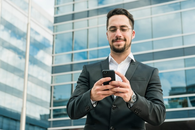 Handsome businessman enjoying text messaging on mobile phone