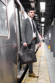 Handsome businessman exiting subway car